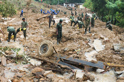 Rescuers search for victims of a landslide.